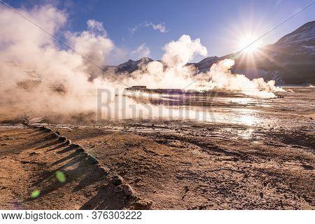 Sunrise At Geyser El Tatio Near San Pedro De Atacama In Chile. Landscape With Gas Smoking And People