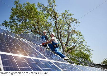 Two Workers In Protective Helmet On Steel Platform Installing Heavy Solar Photo Voltaic Panel On Gre