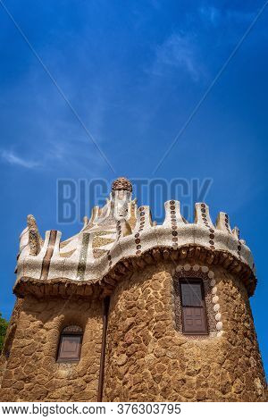 Barcelona, Spain - Jun 10, 2014: Stone House With Mosaic Roof In The Famous Park Guell (parc Guell 1