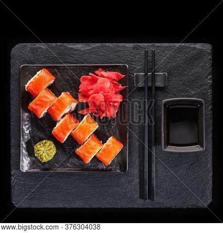 Japanese Restaurant, Sushi Roll On Black Slate. Set With Chopsticks, Ginger And Wasabi On A Dark Bac