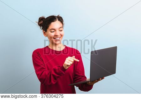 Young Attractive Woman Student With Funny Face Holding A Laptop And Pointing Into It Applaying For U