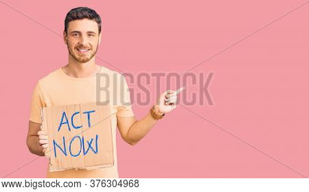Handsome young man with bear holding act now banner smiling happy pointing with hand and finger to the side
