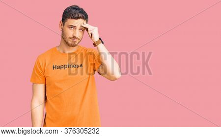 Handsome young man with bear wearing tshirt with happiness word message worried and stressed about a problem with hand on forehead, nervous and anxious for crisis