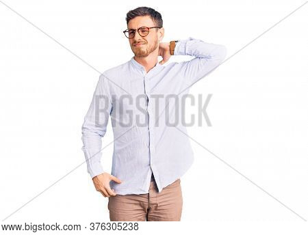 Handsome young man with bear wearing elegant business shirt and glasses suffering of neck ache injury, touching neck with hand, muscular pain