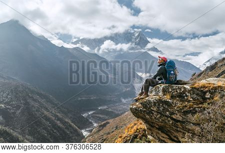 Young Hiker Female Backpacker Sitting On The Cliff Edge And Enjoying Mountain Peaks View During Ever