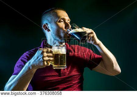 Man Enjoys Drinking And Enjoying Light And Dark Beer On A Dark Green Background