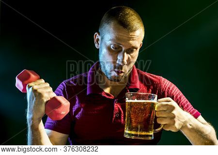 Man Suffers From The Problem Of Choosing Between Drinking Beer And Playing Sports With Dumbbells On