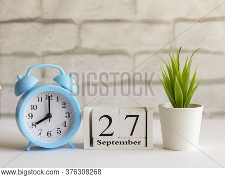 September 27 On A Wooden Calendar Next To The Alarm Clock.september Day, Empty Space For Text.calend