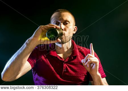 Man Happily Drinks Beer From A Bottle On A Dark Green Background