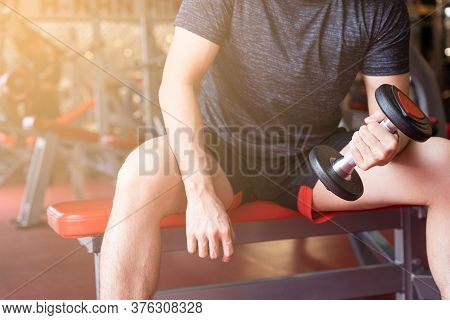 Bodybuilder Working Out With Dumbbell Weights At The Fitness Gym. Female Bodybuilder Doing Exercises