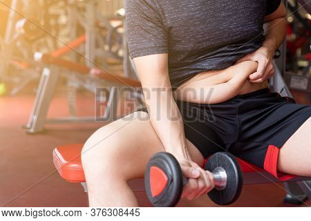 Fat Man Holding Dumbbell And Excessive Fat Belly, Overweight Fatty Belly At Fitness Gym. Diet Lifest