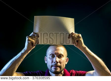 A Man Holds A Paper Poster Above His Head On A Dark Blue Background