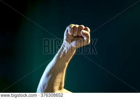 A Raised Hand With A Clenched Fist On A Dark Blue Background