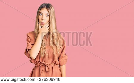 Beautiful caucasian woman with blonde hair wearing summer jumpsuit looking fascinated with disbelief, surprise and amazed expression with hands on chin