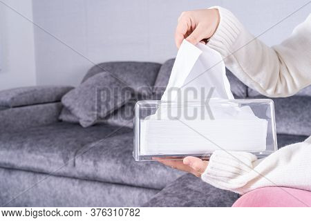 Delicate Female Hands Pulling A White Tissue Paper Out Of A Transparent Crystal Tissue Box On Sofa A