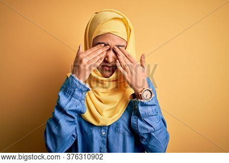 Young beautiful woman with curly hair wearing arab traditional hijab over yellow background rubbing eyes for fatigue and headache, sleepy and tired expression. Vision problem