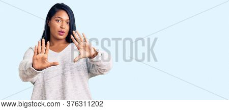Hispanic woman with long hair wearing casual clothes moving away hands palms showing refusal and denial with afraid and disgusting expression. stop and forbidden.