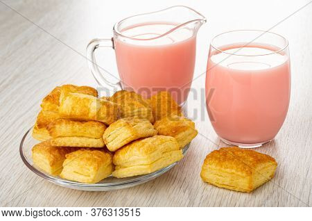 Small Puff Cookies In Saucer, Milk Fruit Drink With Strawberry Juice In Transparent Pitcher And In G