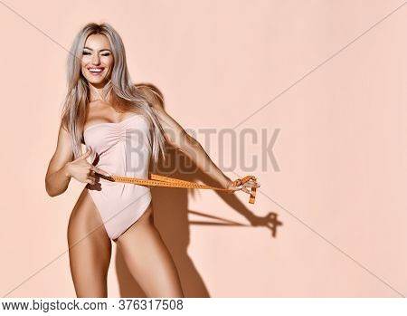 Fitness Perfect Body Weight Loss Concept. Blonde Slim Woman Holds Tape Measure Measuring Waist Smili