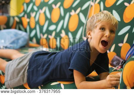Cute Noisy Boy Scream Very Loud In A Temper Tantrum Liying On Sofa. Children Education, Development