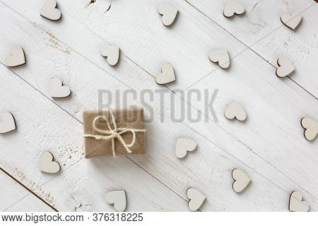 Handmade Gift In Kraft Paper On A White Background. Wooden Decorative Hearts Around Gift.