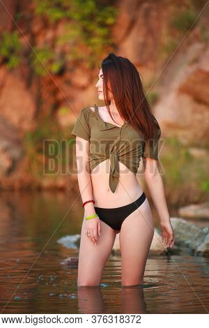Charming Sensual Carefree Brunette Girl In The Water Of A Wild Lake On A Rock Background In The Ligh