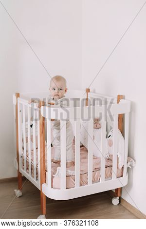 Cute Smiling Little Baby Standing In Crib At Home.