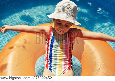Cheerful Kid In A Colorful Swimming Suit Relaxing On An Inflatable Ring Floating In A Pool Having Fu