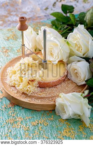 Texture Of Cheese Monk Head. Swiss Cheese With Crumbs On A Wooden Surface And A Decorative Tableclot