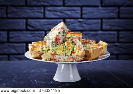 Slices Of Quiche With Salmon Asparagus Cheese Filling On A Cake Stand On A Concrete Table With A Bri