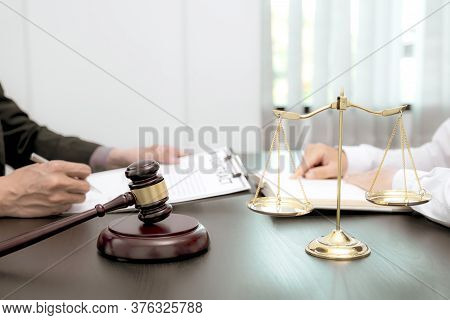 The Scales Of Justice And Judges Gavel Standing In Front Of The Male Lawyer Who Is Providing Service