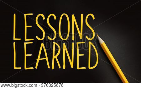Lessons Learned Text In Yellow On Black And Pencil Besides. Education Or Risk Management In Business