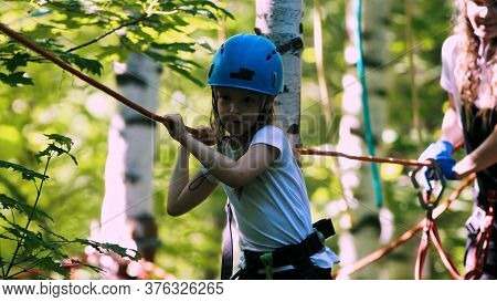 Rope Adventure - A Girl With An Insurance Hook Attached To The Rope Walking On Rope Bridge