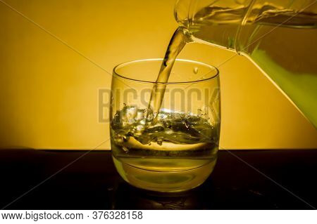 Elegant Shot Of A  Pitcher Pouring Water In A Glass On A Dark Background