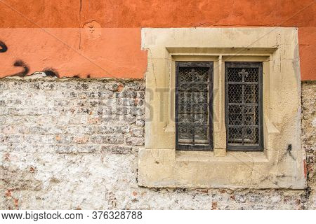 Close Up Shot To A Corroded Orange Wall Texture With Bricks And An Old Window With Iron Grill And Wo