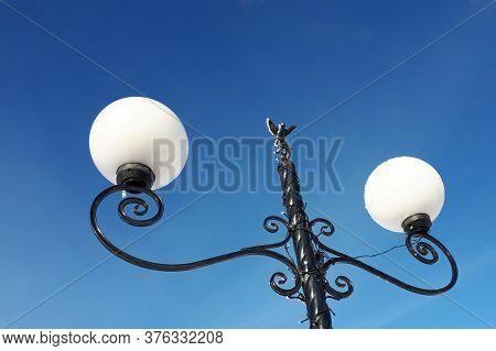 Lantern Against A Clear Blue Sky. Hoarfrost On The Lantern. Little Bird Decorates A Lantern