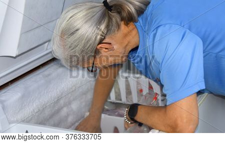 Senior Woman Digs Into A Chest Freezer.  She Is Defrosting And Cleaning Out Old And Expired Frozen F