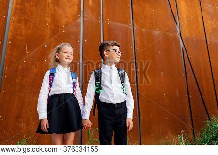 Two Schoolchildren Boy And Girl, Little Schoolchildren, Little Schoolchildren Are Returning From Sch