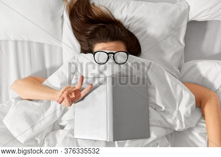 people, bedtime and rest concept - woman lying in bed under white blanket or duvet with book and glasses showing peace hand sign
