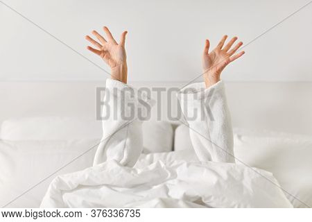 gesture, comfort and morning concept - hands of young woman in hotel robe lying in bed and stretching at bedroom