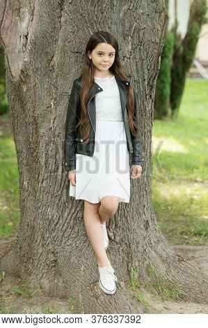 Cute And Trendy. Small Child Stand At Tree In Park. Fashion Look Of Little Model. Designer Kidswear