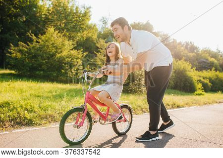 Happy Father Rejoices That Her Daughter Learned To Ride A Bike, Father Holding His Daughter While Sh