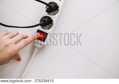 A Woman Turns On An Electric Surge Protector. Protection Of Household Appliances From Electrical Int