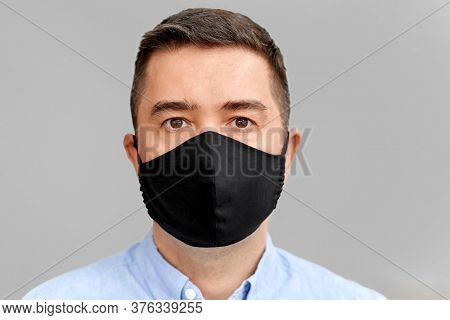 health protection, safety and pandemic concept - portrait of middle-aged man in black reusable face protective mask over grey background