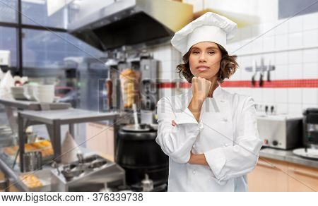cooking, culinary and people concept - female chef in toque thinking over restaurant or kebab shop kitchen background