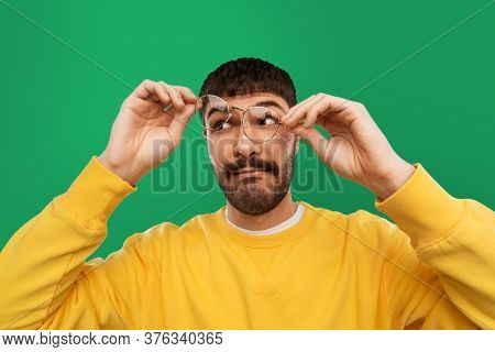 vision and people concept - goofy young man in glasses and yellow sweatshirt over emerald green background