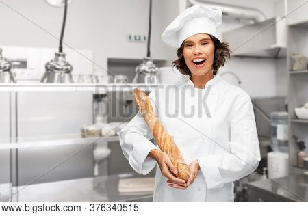cooking, culinary and bakery concept - happy smiling female chef or baker in toque holding french bread or baguette over restaurant kitchen background