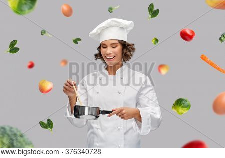 food cooking, culinary and people concept - happy smiling female chef in toque with saucepan over fruits and vegetables on grey background
