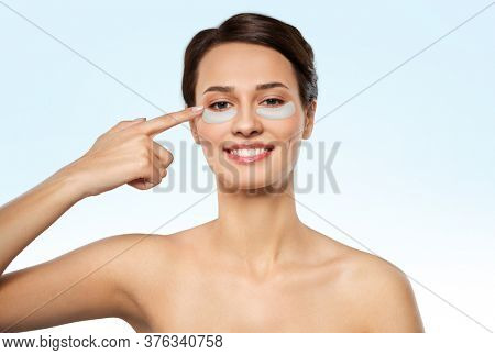 beauty, cosmetology and rejuvenation concept - beautiful young woman with hydrogel under-eye patches over blue background