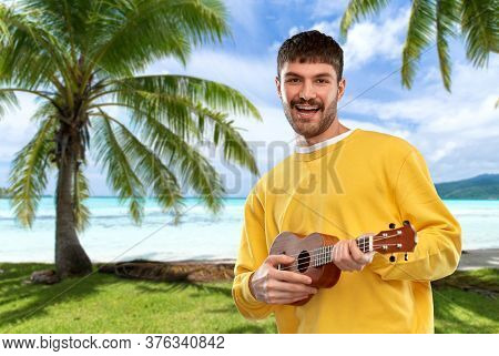 music, leisure and summer holidays concept - smiling young man in yellow sweatshirt playing ukulele guitar over tropical beach background in french polynesia